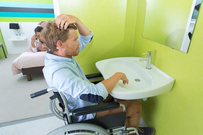 mężczyzna korzystający z łazienki dla osób niepełnosprawnych